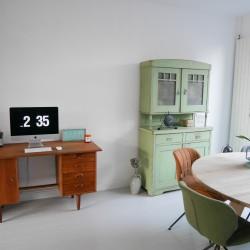 Woonkamer met vintage bureau en oude groene buffetkast